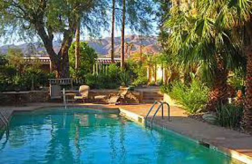 Pool at resort in Desert Hot Springs, California. The pool is surrounded by lush vegetation, and there is a mountain in the background.